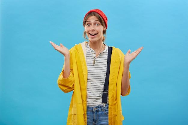 Mooie huisvrouw met rode hoed, gele jas en jean overall die haar handen ophaalt, wenkbrauwen opheft van verrassing, mond opent met gevoel wonder poseren over blauwe muur met kopie ruimte