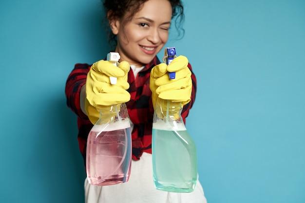 Mooie huisvrouw regisseert schoonmaaksprays alsof ze fotografeert vanuit een pistool dat kwaadwillig glimlacht en één oog bedekt naar de camera focus op handen in handschoenen met sprays