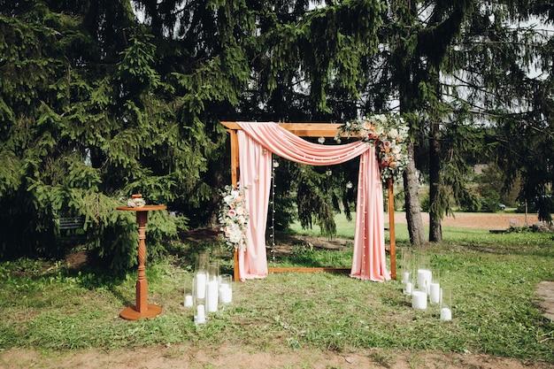 Mooie huwelijksboog met kaarsen in de tuin.
