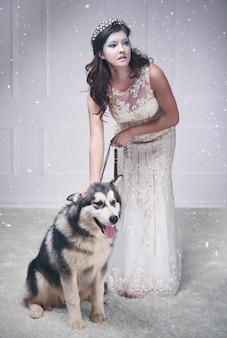 Mooie ijskoningin met hond onder vallende sneeuw