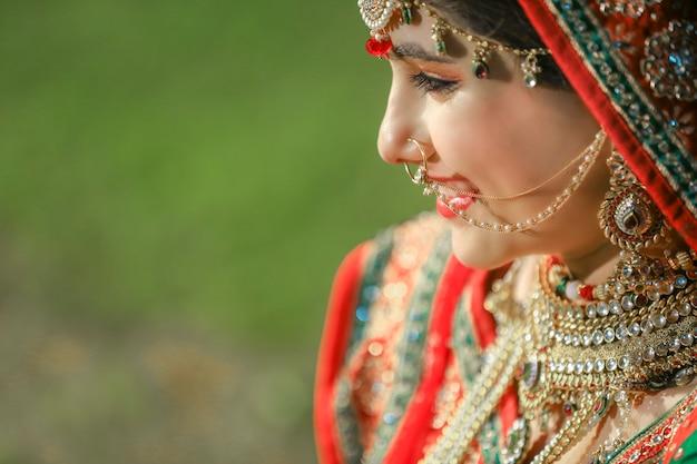 Mooie indiase bruid met sari en gouden sieraden op indiase bruiloft