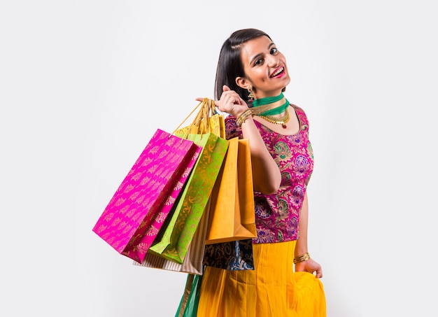 Mooie indiase jonge meid die veel boodschappentassen vasthoudt terwijl ze traditionele etnische kleding draagt. geïsoleerd op witte achtergrond