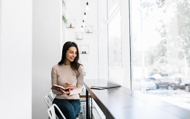 Mooie indiase vrouw freelancer met behulp van laptop, notities schrijven, werken vanuit huis. aziatische student studeren, examenvoorbereiding, afstandsonderwijs