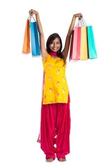 Mooie indiase vrouw, gekleed in een traditionele saree met boodschappentassen