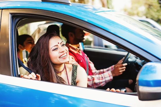 Mooie indiase vrouw kijkt uit het raam van de auto looking