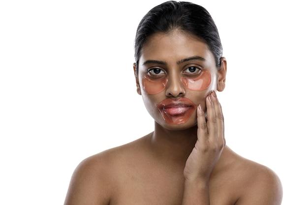 Mooie indiase vrouw met hydraterende ooglapjes en lipmasker op haar gezicht. geïsoleerd op wit.