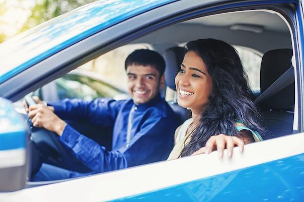 Mooie indiase vrouw rijdt in een blauwe auto met chauffeur