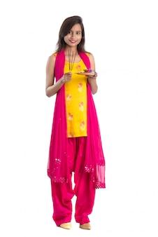 Mooie indische jonge poojathali van de meisjesholding of het uitvoeren van verering op wit