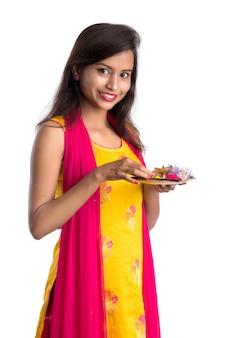 Mooie indische jonge poojathali van de vrouwenholding of het uitvoeren van verering op wit