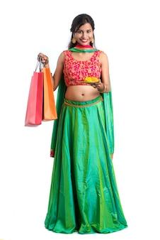 Mooie indische jonge vrouwenholding en het stellen met het winkelen zakken en poojathali op een witte muur