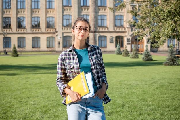 Mooie indische studente dichtbij de universiteit. jonge donkerbruine vrouw die met glazen boeken houdt.