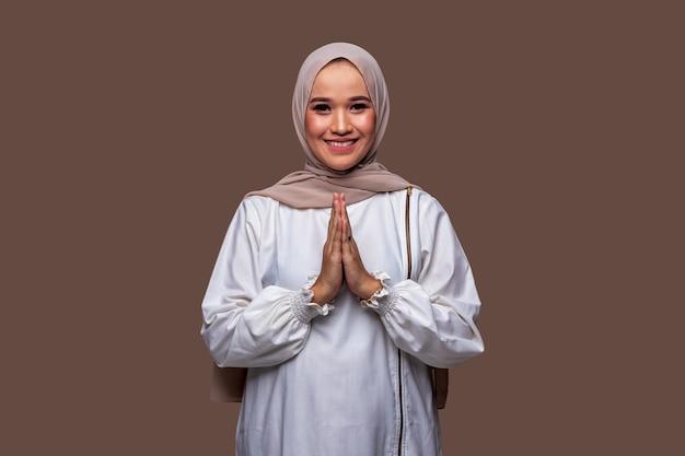 Mooie indonesische moslimvrouw groeten gebaar typisch voor ramadan en vieren eid al-fitr