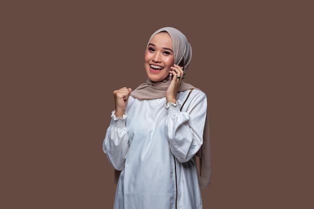 Mooie indonesische vrouw die hijab draagt, krijgt het goede nieuws op haar mobiel met een glimlach en succesvolle uitdrukking geïsoleerd op effen achtergrond