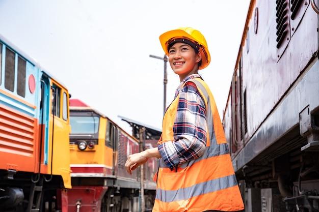 Mooie ingenieur vrouw controleert treinstation garage planten met veiligheidshelm