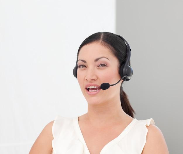 Mooie internationale zakenvrouw op een headset lacht