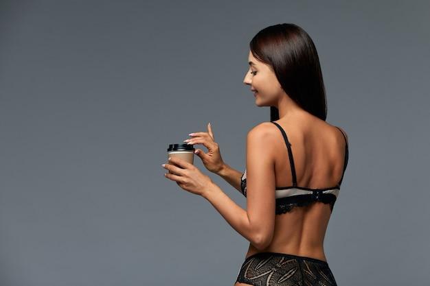 Mooie italiaanse vrouw met koffie in lingerie op grijze achtergrond met kopie ruimte reclamebanner goede en krachtige ochtend concept meisje en koffie - goed humeur in de ochtend