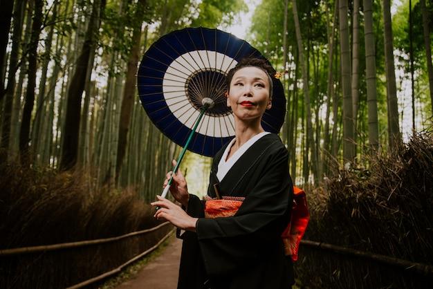 Mooie japanse hogere vrouw die in het bamboebos loopt