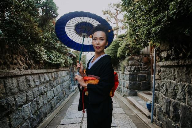 Mooie japanse hogere vrouw die in het dorp loopt. typische japanse traditionele levensstijl