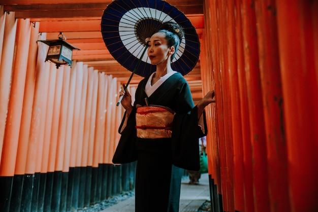 Mooie japanse hogere vrouw die in het heiligdom van fushimiinari lopen in kyoto
