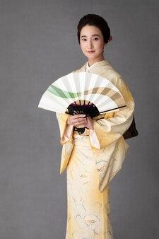 Mooie japanse vrouw met een minimalistische handventilator