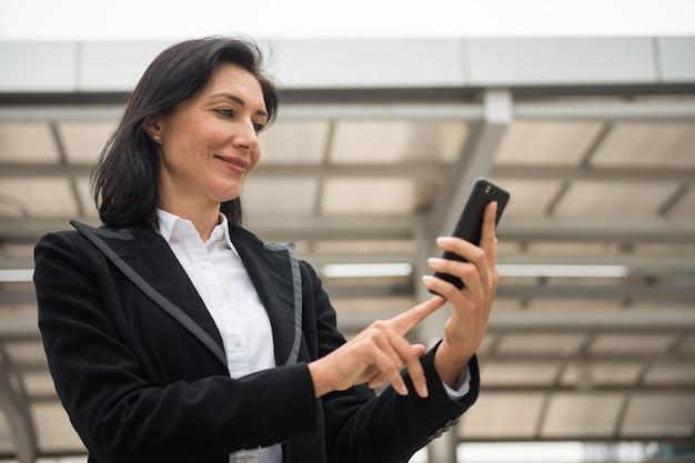 Mooie jaren 50 lachende amerikaanse senior zakenvrouw surfen op internet en chatten op mobiele smartphone in de stad. zakelijke discussie door zakelijke app op de telefoon.