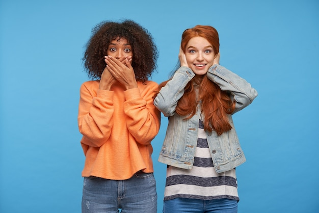 Mooie jonge aantrekkelijke vrouwen die verschillende emoties uitdrukken tijdens het kijken, hun mond en oren bedekken met opgeheven handen terwijl ze over de blauwe muur staan