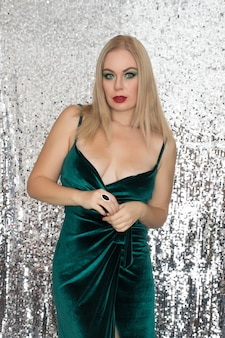 Mooie jonge ademende blonde heldere vrouw in groene fluwelen kleding over glanzend zilver