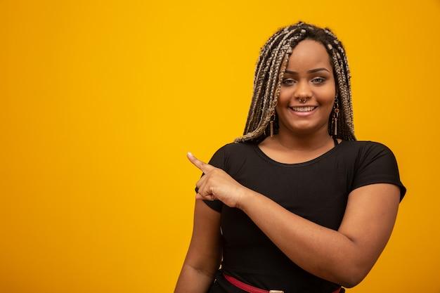Mooie jonge afrikaanse amerikaanse vrouw die met ontzorgen haar de vinger op geel richten