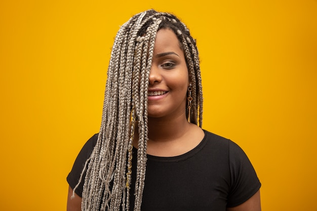 Mooie jonge afrikaanse amerikaanse vrouw met ontzettingshaar op geel