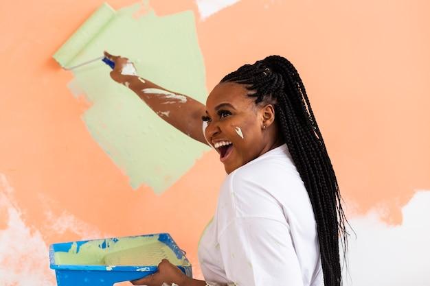 Mooie jonge afrikaanse amerikaanse vrouw met verfroller binnenshuis. herinrichting, renovatie