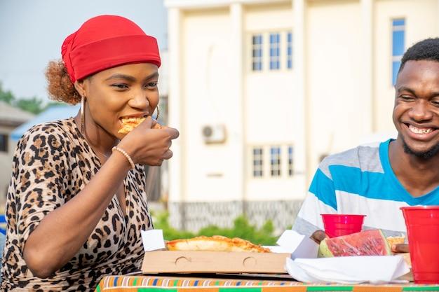 Mooie jonge afrikaanse dame die pizza eet, zittend met een vriend