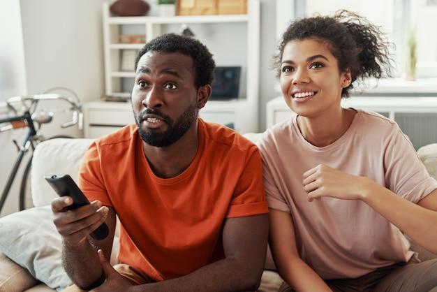 Mooie jonge afrikaanse koppels die tv kijken en glimlachen terwijl ze thuis tijd doorbrengen