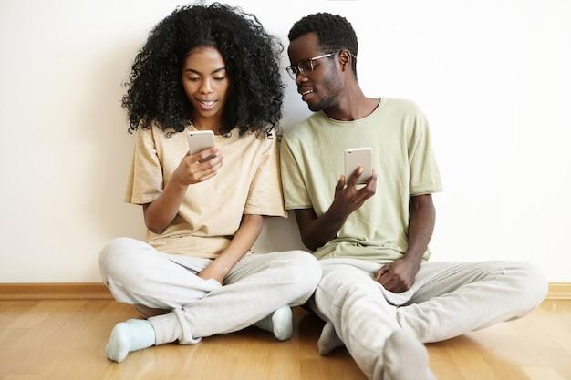 Mooie jonge afrikaanse paar genieten van gratis wi-fi thuis, met behulp van online apps op hun mobiele telefoons