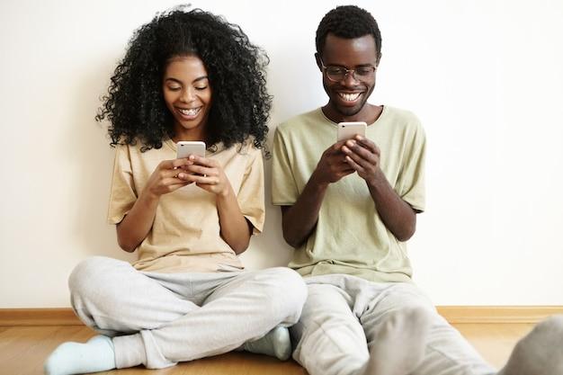 Mooie jonge afrikaanse paar genieten van online communicatie thuis, zittend op de vloer, met behulp van elektronische gadgets