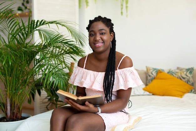 Mooie jonge afrikaanse vrouw die een boek op het bed leest