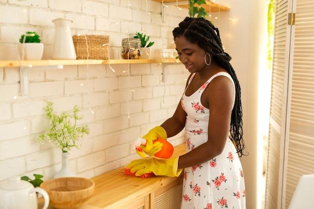 Mooie jonge afrikaanse vrouw die het huis schoonmaakt