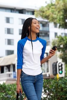 Mooie jonge afrikaanse vrouw die in openlucht in de stad met cellphone loopt