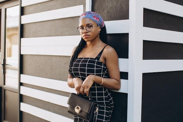 Mooie jonge afrikaanse vrouw, gekleed in modieuze jurk poseren op straat. afro kapsel