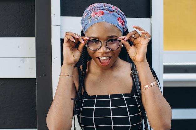 Mooie jonge afrikaanse vrouw in de glazen die het modieuze kleding stellen op de straat dragen. afro kapsel
