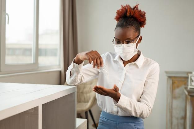 Mooie jonge afrikaanse vrouw in glazen in een medisch masker met een antisepticum in haar handen