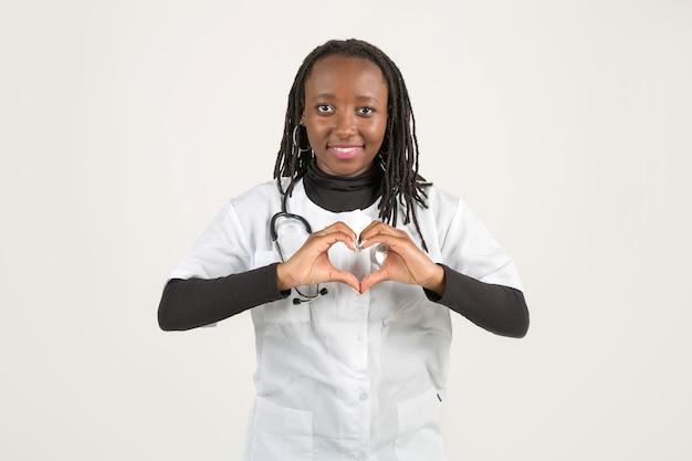 Mooie jonge afrikaanse vrouw in medische kleding met handgebaar