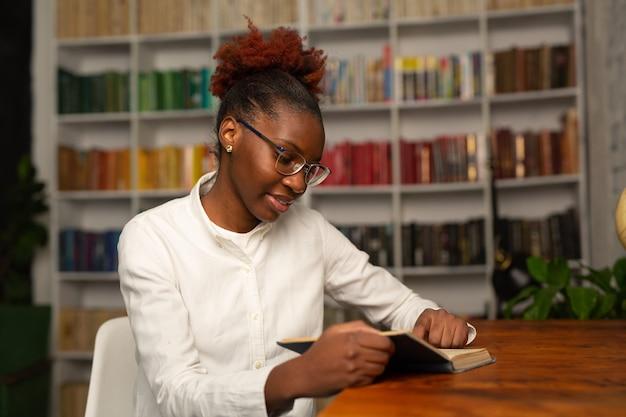 Mooie jonge afrikaanse vrouw in wit overhemd lezen van een boek in de bibliotheek