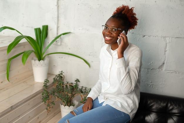 Mooie jonge afrikaanse vrouw in wit overhemd met mobiele telefoon