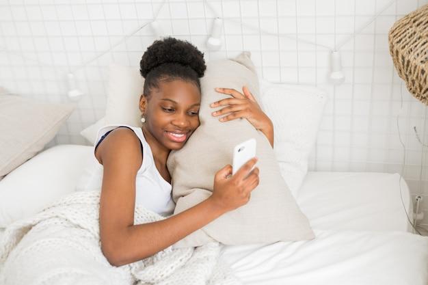 Mooie jonge afrikaanse vrouw ligt op een wit bed met een telefoon