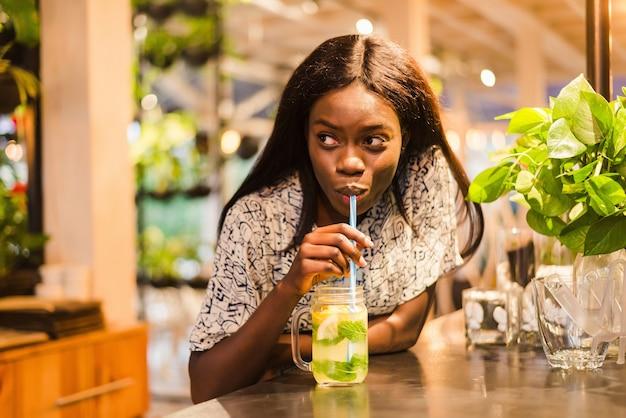 Mooie jonge afrikaanse vrouw met limonade in café