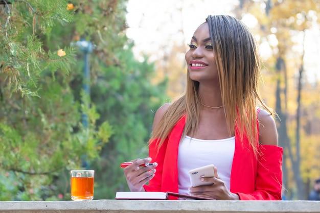 Mooie jonge afrikaanse vrouw met telefoon en rode pen in haar handen