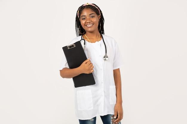 Mooie jonge afrikaanse vrouw op een witte achtergrond in een medische jurk met een map