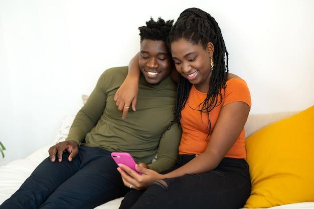 Mooie jonge afrikaanse zitten op bed met mobiele telefoon