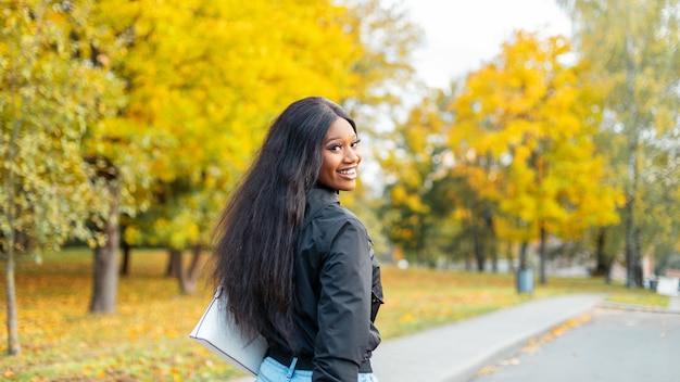 Mooie jonge afro-amerikaanse meid met een glimlach in modieuze kleding loopt in een herfstpark met verbazingwekkende gele bladeren