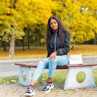 Mooie jonge afro-amerikaanse vrouw in modieuze kleding zittend op een park met gele herfstbladeren